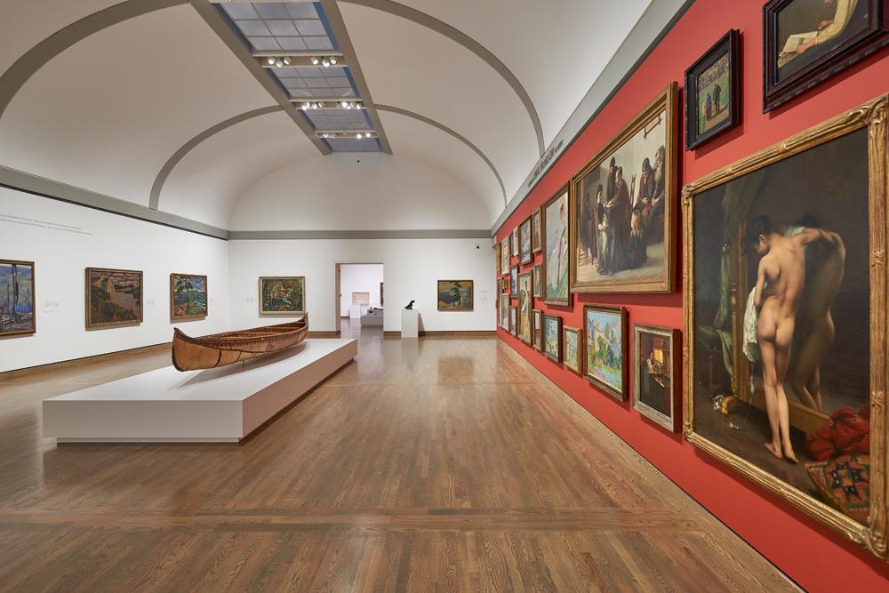 Un Salon canadien aux murs pratiquement couverts de tableaux, du sol au plafond